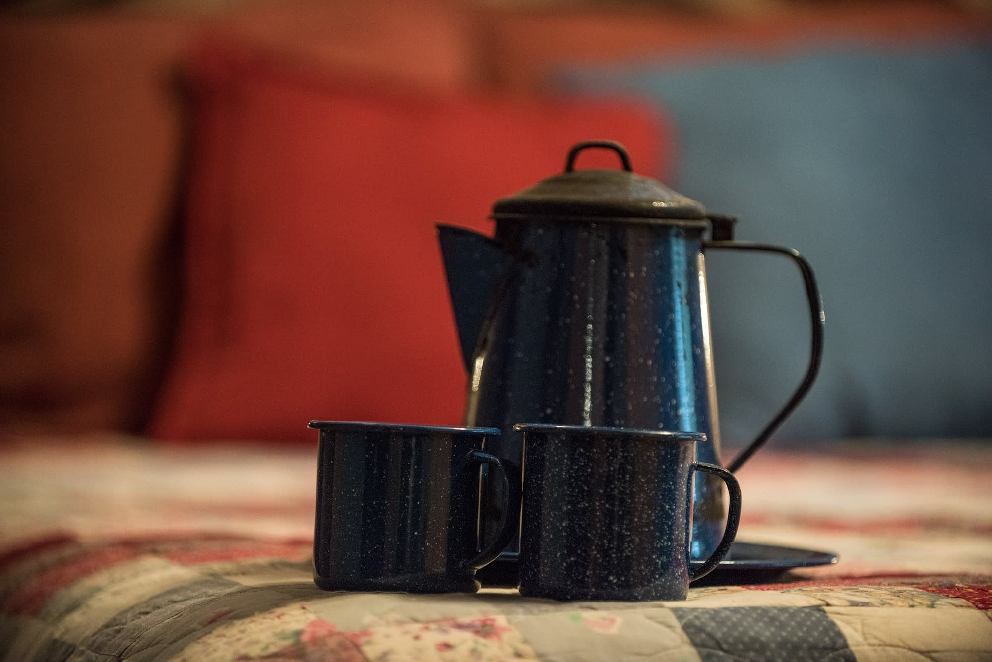 blue camp cups and coffee pot on quilt