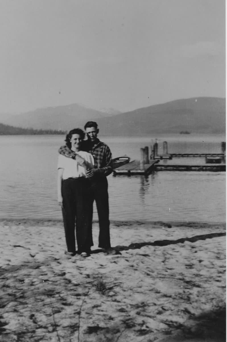 Black and White photo of a man and woman standing by a lake with their arms around each other