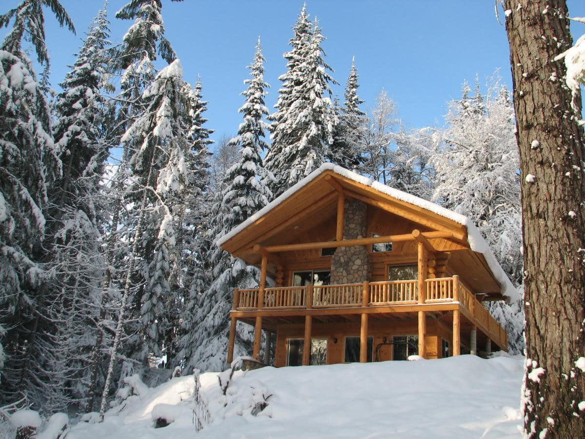 two story log cabin called the Meadow View Cabin sitting on a snowy hill in the forest at Western Pleasure Guest Ranch