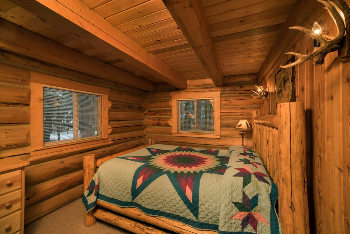 Western Pleasure Guest Ranch rustic cabin bedroom with log bed and teal quilt