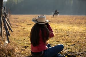 Photographer sitting on the ground taking a photo of a rider in the field