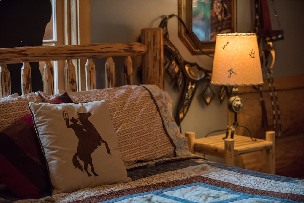 Log bed with pillows and quilt in John Wayne themed room lamp in the background