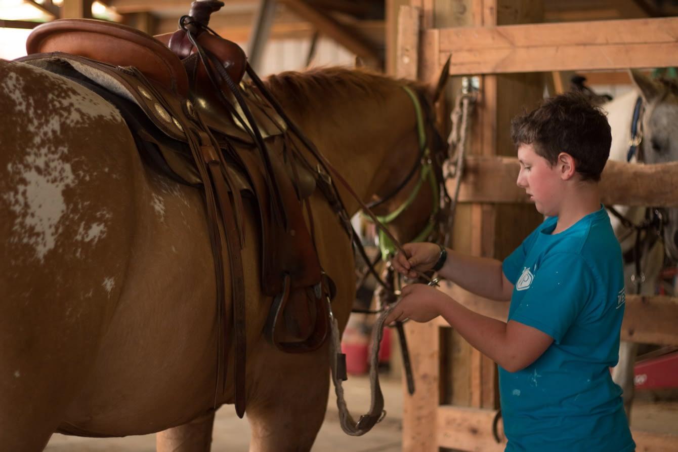 Youth Horsemanship Program with boy saddling his horse