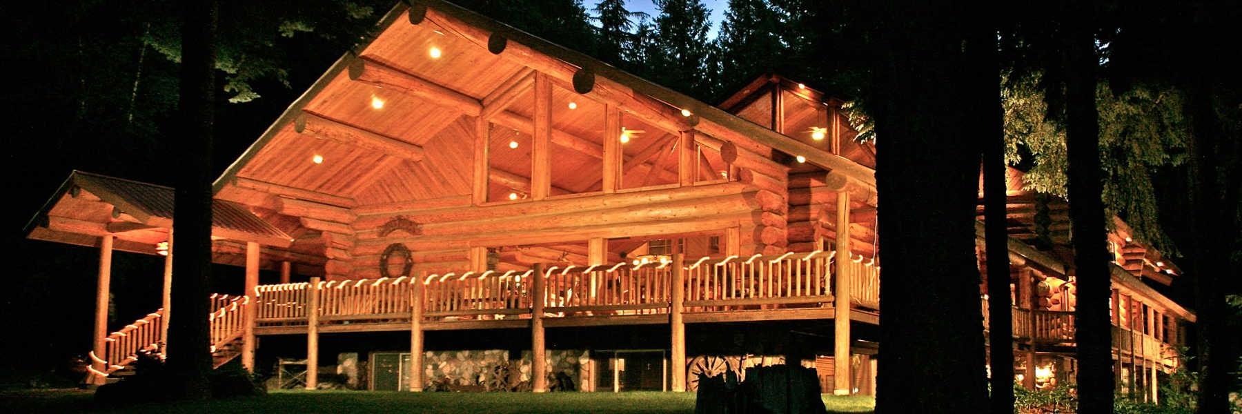 large log Lodge lit by lights at night