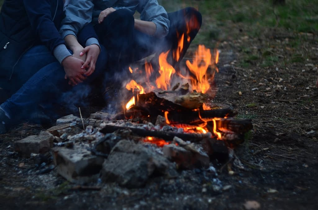 Fall travel campfire with couple holding hands