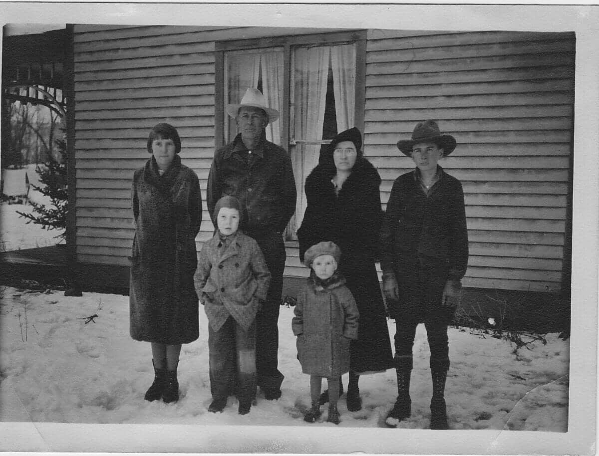 old black and white photo of a family of 6 standing in front of an old house in the snow