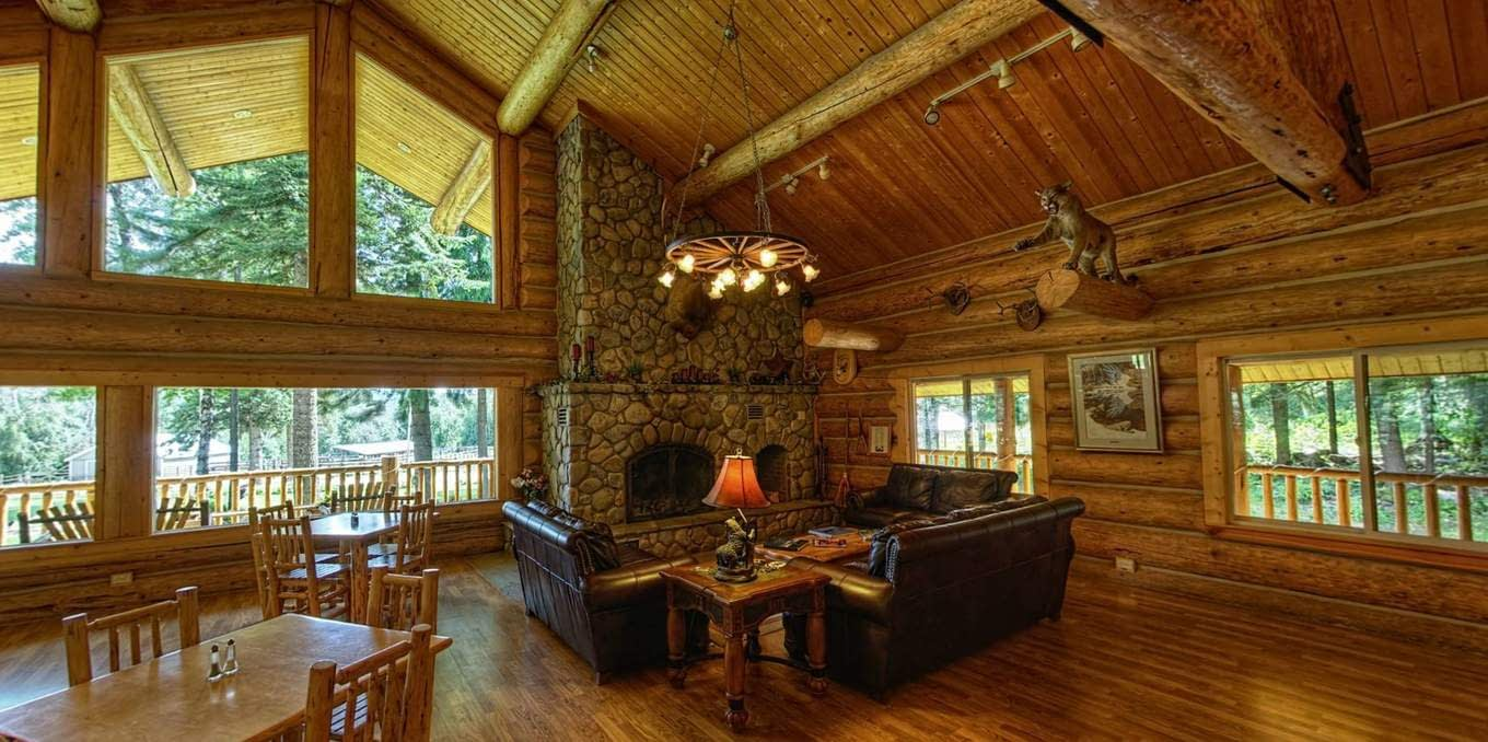 Great room in the log lodge at Western Pleasure Guest Ranch with leather couches and river rock fireplace