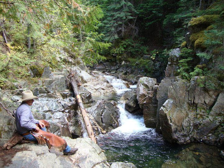 Cowboy sitting on rocks looking our at a small waterfall