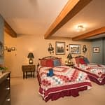 Guest room with two double beds with quilts antique decorations on the walls