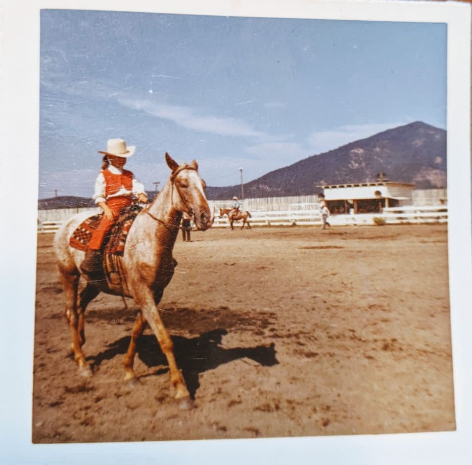 Vintage photo of little girl in red and white riding an Appaloosa in an arena