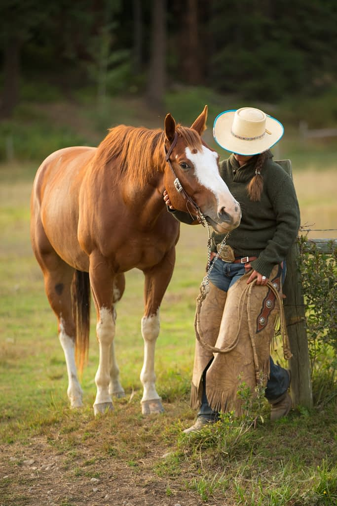 Cowgirl wearing a hat with sorrel horse by a fence