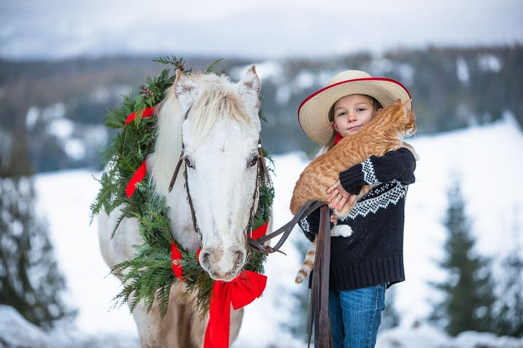 little girl in cowboy hat holding an orange cat white pony standing next to her with a Christmas wreath around its neck.