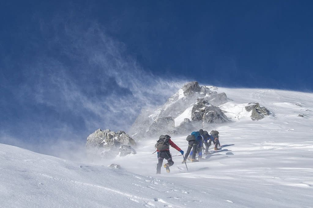 Adventure travel of four men climbing a wind-blown snow-covered mountain summit.