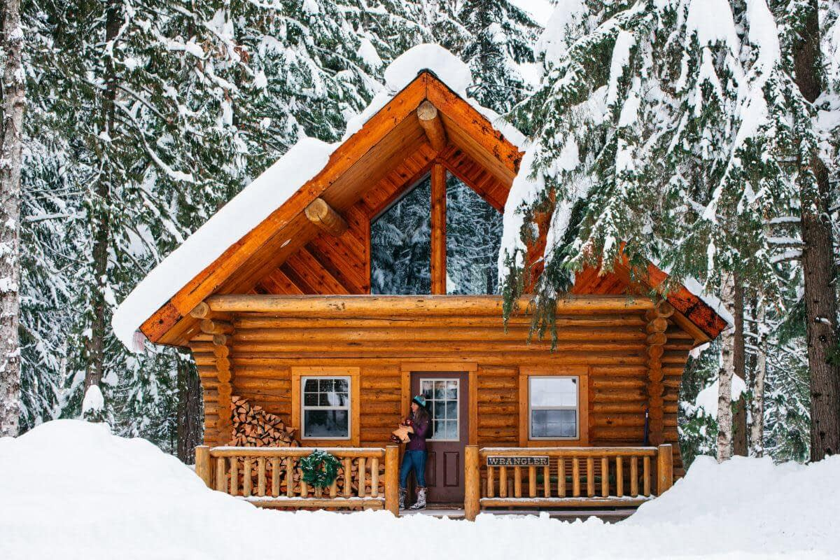log cabin covered in snow covered forest with woman on the deck holding firewood