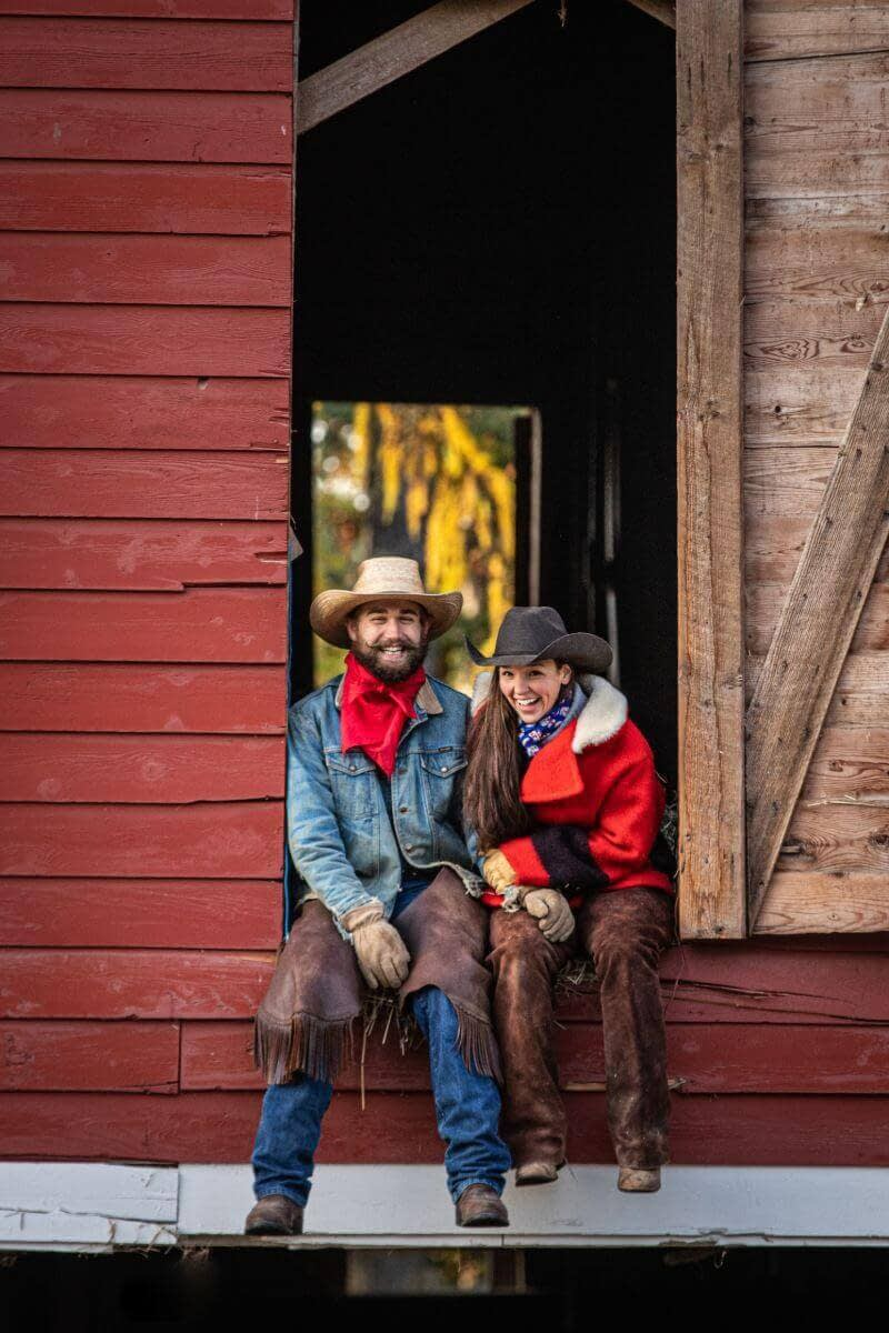 couple wearing cowboy hats sits in the doorway of a red barn
