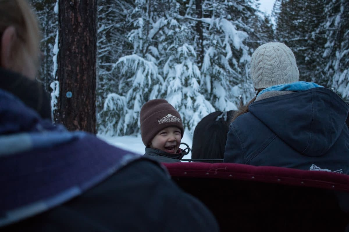 little boy with a hat on smiling while riding on a sleigh through the snow covered forest