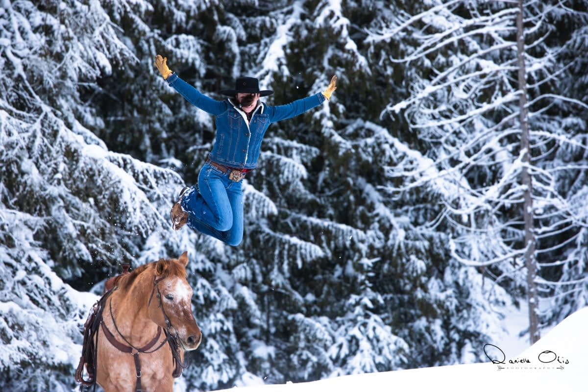 Cowgirl with her hands in the air jumping off horse into snow bank