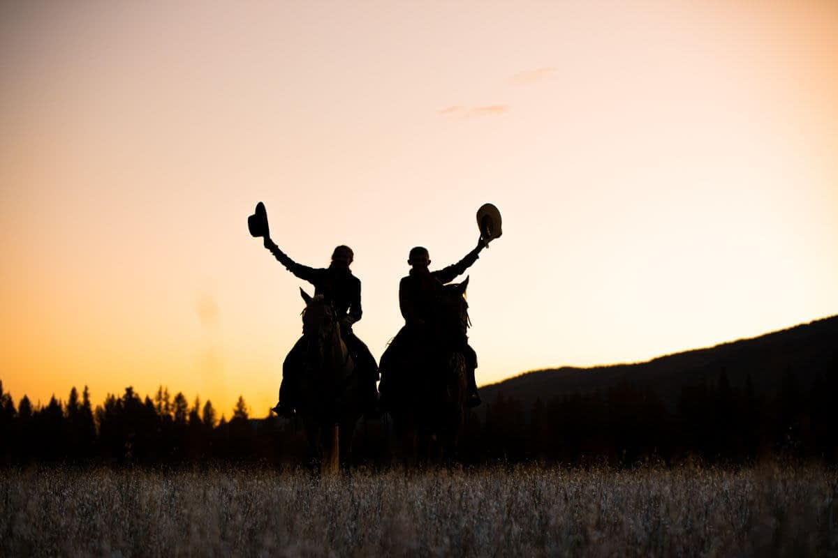 silhouette of cowboys on horseback with hats in the air and sunset behind them