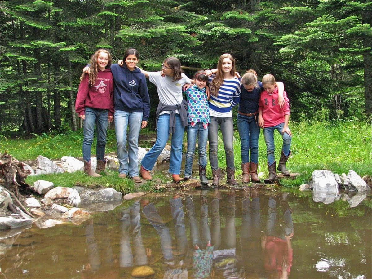 children standing in line with arms around each other next to a pond
