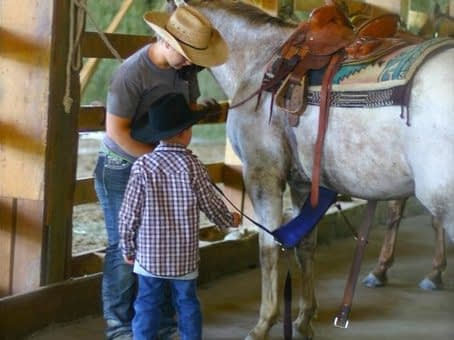 cowgirl teaching child how to saddle a horse at Western Pleasure Guest Ranch Youth Horsemanship Program