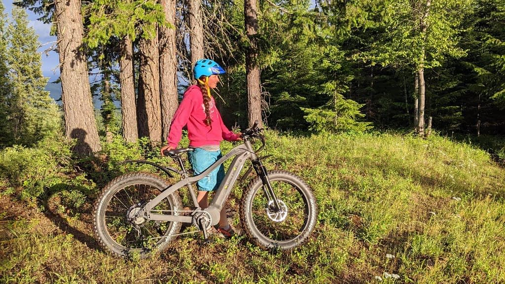 A woman stands next to a Quietkat eBike while taking a rest on a mountain ride