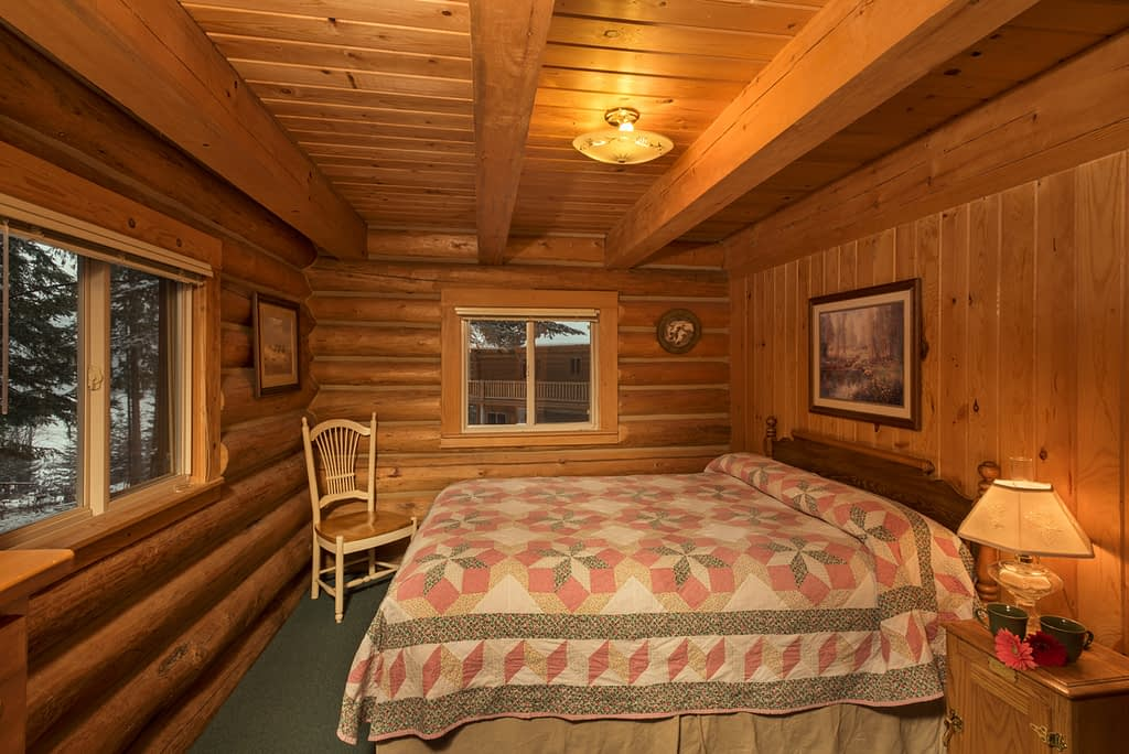 Private bedroom in log cabin with quilted bed coffee cups on side table