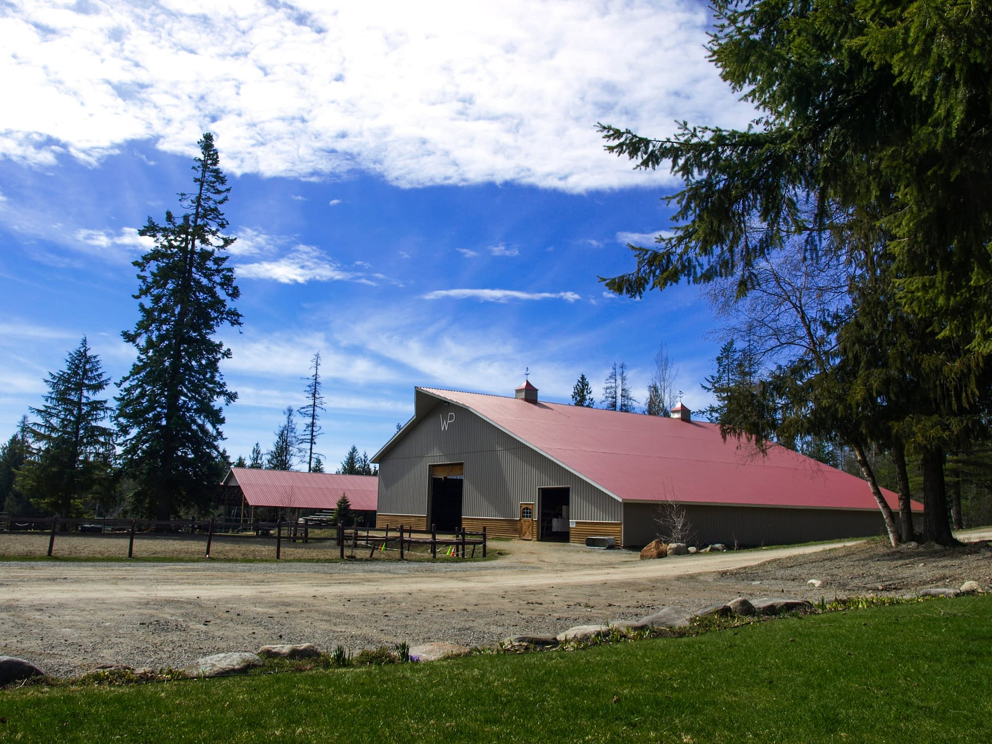 Large grey indoor arena barn with red roof and blue sky above
