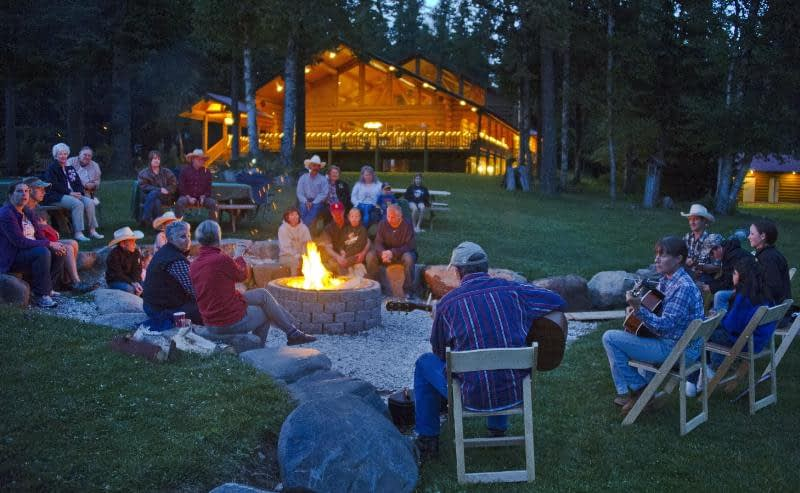 people sitting around a campfire listening to musicians play cowboy music