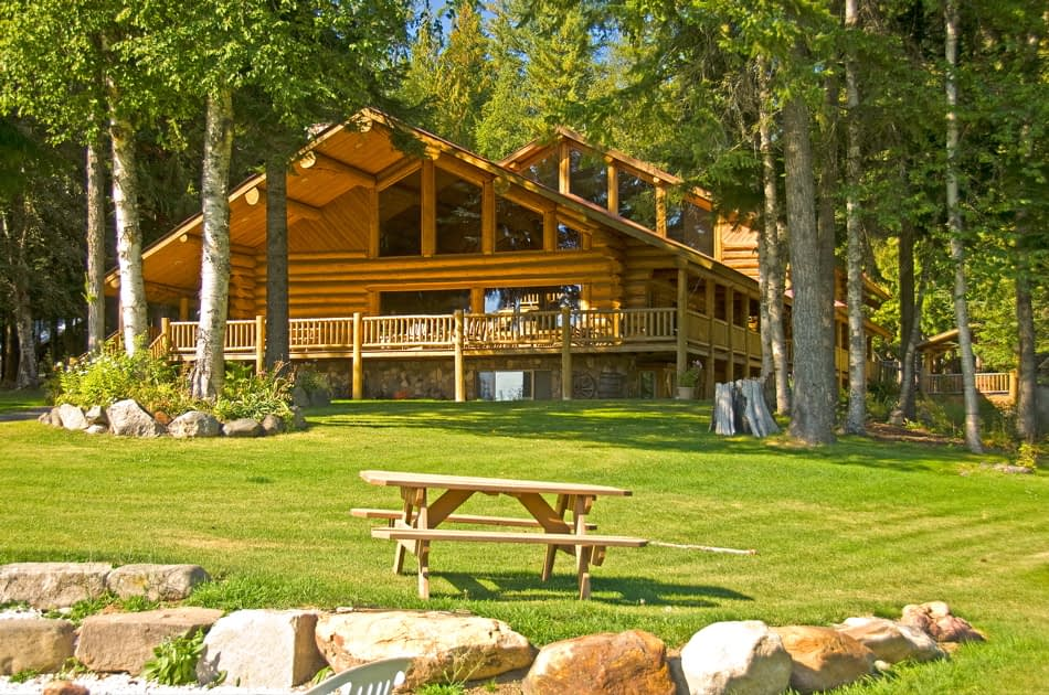 Large log lodge with green lawn and a picnic table