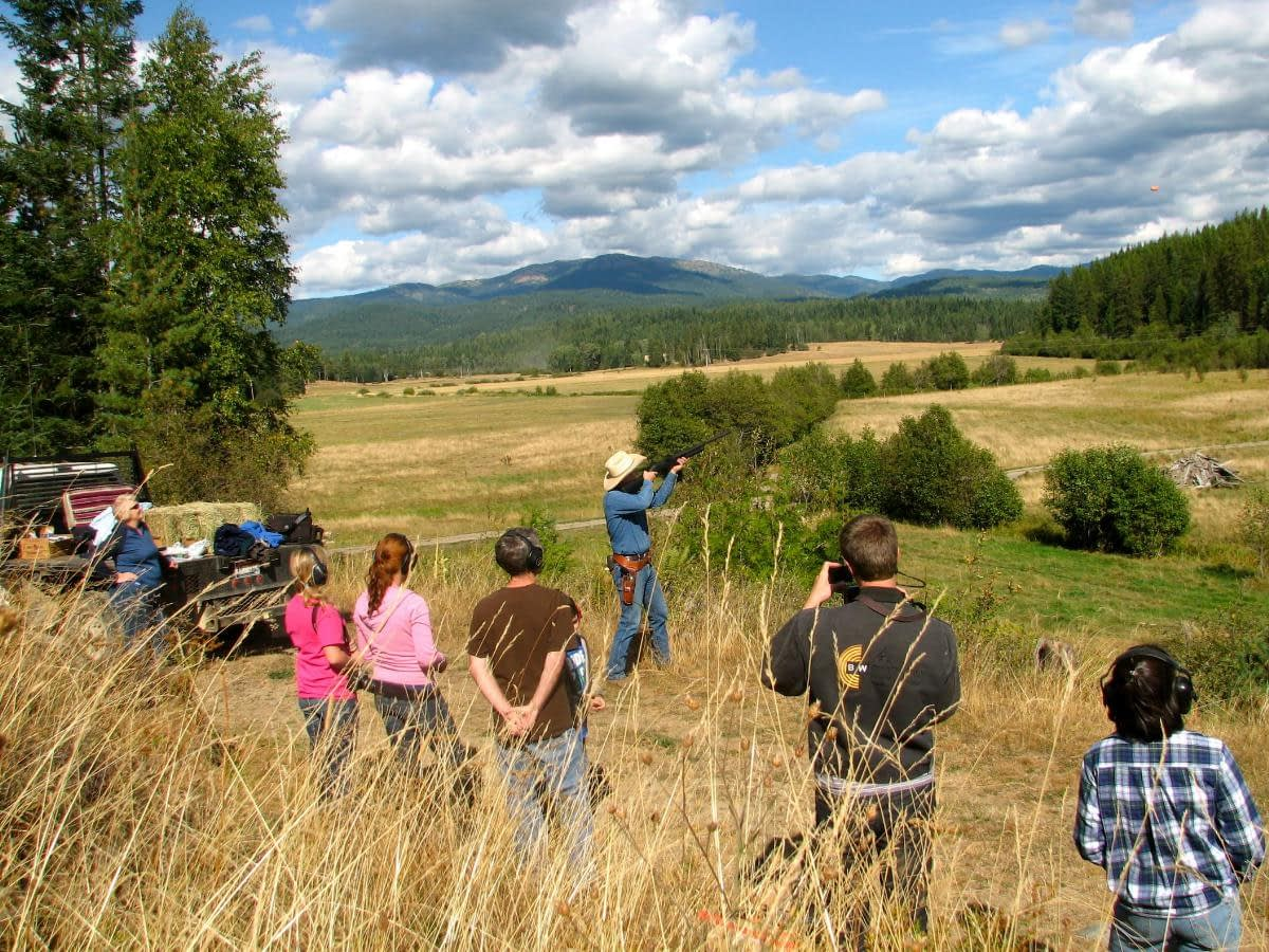 a crowd watches a cowboy shooting Shooting Clay Pigeons