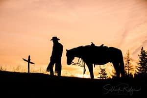 Silhouette of cowboy and horse at cross
