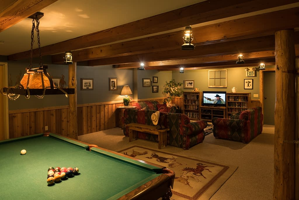 Lodge Rec room with green pool table, lantern lights, couches, tv and movies