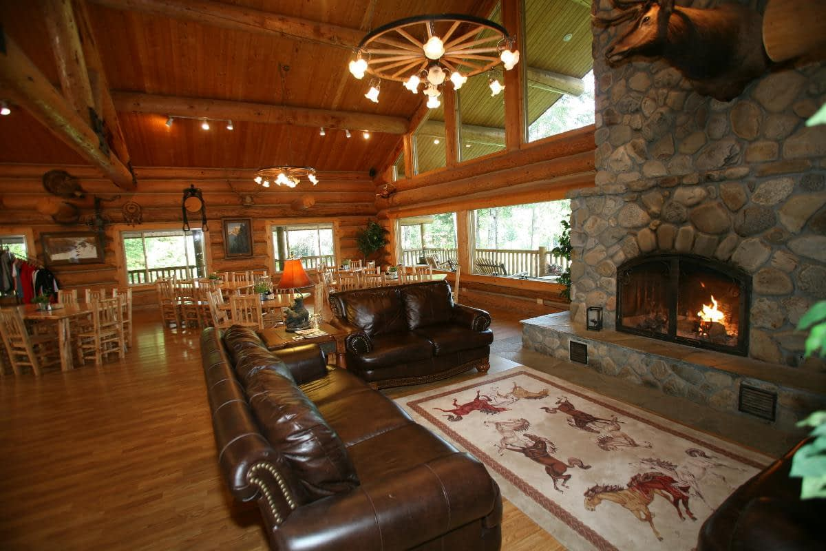 large river rock fireplace with leather couches and log tables and chairs