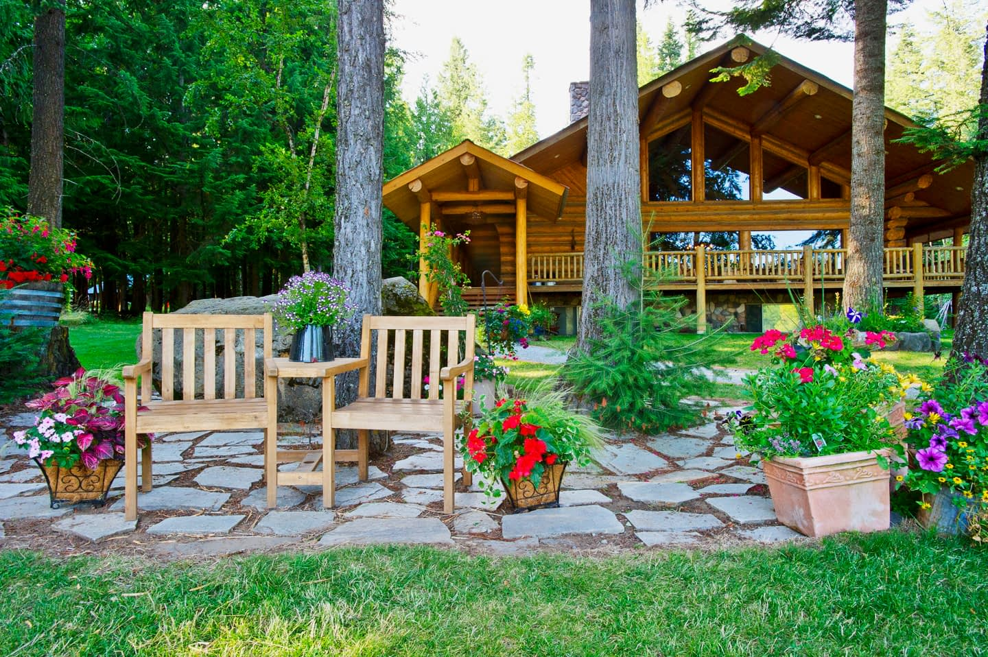 Large log lodge in the background with relaxing chairs in the foreground with flowers around them
