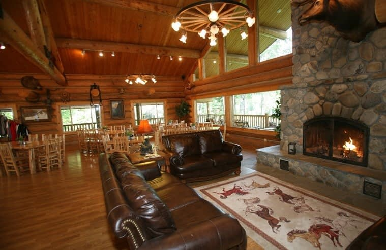 Lodge great room with warm fire burning in river rock fire place