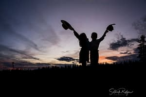 Silhouette of cowboy and cowgirl holding their hats up in the air